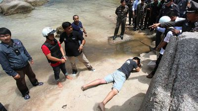Wearing white helmets and handcuffs, the two Burmese men re-enacted the rape and murders they are alleged to have confessed to.