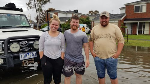The heroic trio snapped in floodwaters outside the rescue.