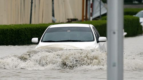 A man drives his car through a flooded street in Gulf emirate of Dubai, United Arab Emirates on 9 March 2016. (AAP)