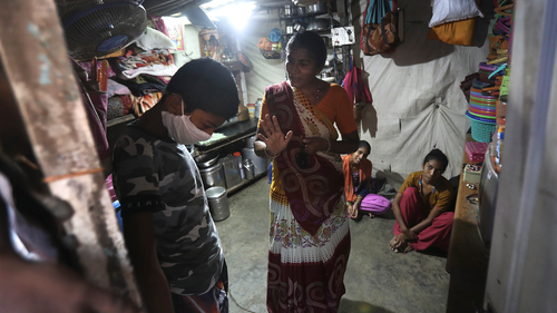 Mina Ramesh Jakhawadiya, center, tells her son Ritik Ramesh, left, not to go out and play because of the coronavirus and be in the house in Mumbai, India, March 30, 2020. Jakhawadiya makes a living selling cheap plastic goods with her husband on the streets of Mumbai. For her, the order means 21 days in a 6-by-9 foot room with five people, no work, a couple days of food and very less cash. (AP Photo/Rafiq Maqbool)