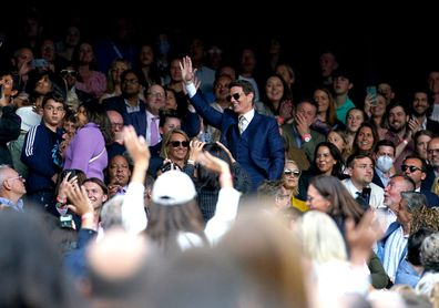 Tom Cruise (centre) waves to the fans as he watches the ladies' singles final between Ashleigh Barty and Karolina Pliskova on centre court on day twelve of Wimbledon at The All England Lawn Tennis and Croquet Club, Wimbledon. Picture date: Saturday July 10, 2021. (Photo by Adam Davy/PA Images via Getty Images)