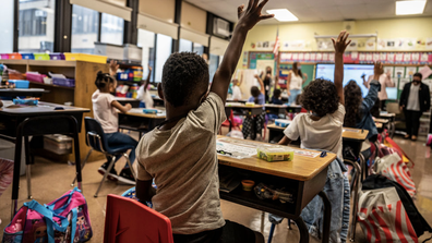 A child raises his hand in class on the first day of school at Bayview Avenue School of Arts and Sciences in Freeport, New York on September 1, 2021.
