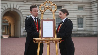 Footmen Stephen Kelly and Sarah Thompson bring out the easel in the forecourt of Buckingham Palace in London to formally announce the birth of a baby boy to the Duke and Duchess of Sussex