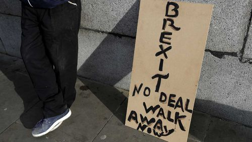A banner leans on a wall near to parliament in London.