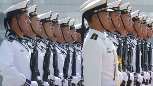 Chinese People's Liberation Navy sailors stand in formation on the deck of a type 054A guided missile frigate 'Wuhu'.