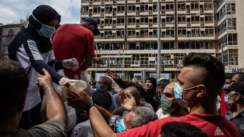 People wait to receive food and masks from the back of an aid truck on August 13, 2020 in Beirut, Lebanon