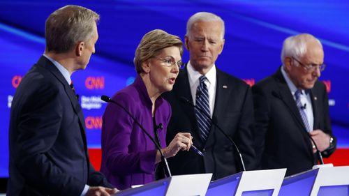 Elizabeth Warren speaks during the debate as Tom Steyer, Joe Biden and Bernie Sanders.