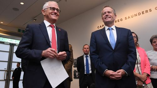 Despite the animosity between the two, Prime Minister Malcolm Turnbull and Opposition Leader Bill Shorten were all smiles today at the commemoration of the repatriation of the Long Tan Cross at the Australian War Memorial in Canberra (Image: AAP)