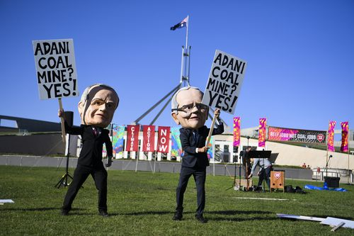Anti-Adani coal mine protesters wearing big puppet heads of Scott Morrison and Bill Shorten are making a lot of noise outside parliament.