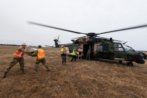 Soldiers and ground staff at at Bairnsdale Airport load a Navy MRH-90 helicopter with food and water to be airlifted to Cann River in Gippsland, Victoria