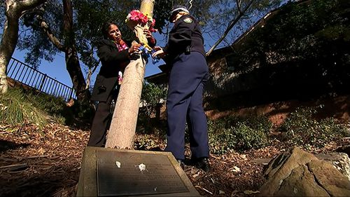 Julianne Szabo hangs flowers on a tree planted in memory of her son may years ago. (9NEWS)