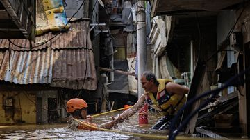 An Indonesian rescue worker helps his colleague as they navigate through a flooded neighbourhood on January 2, 2020 in Jakarta, Indonesia.