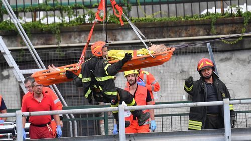 Rescue workers lift a person out of the rubble of the collapsed bridge.