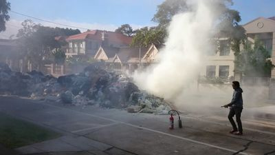 Fire and Rescue NSW extinguish burning garbage. (9NEWS)