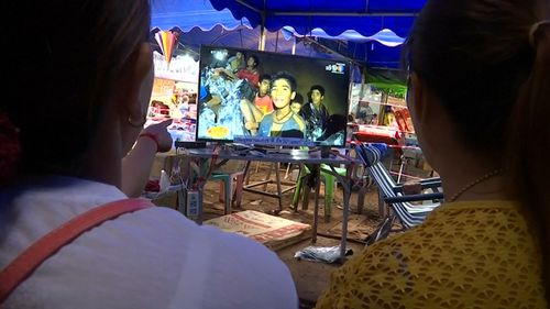 Mums of the boys watch a live video link of their sons from the makeshift camp above ground. Picture: Reuters.
