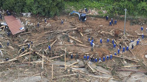 Rescue workers search for missing persons at a site of a landslide following a heavy rain in Tsunagi town, Kumamoto prefecture, southern Japan Saturday, July 4, 2020