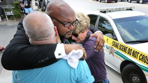 Kelvin Cobaris, a local clergyman, consoles Orlando city commissioner Patty Sheehan, right, and Terry DeCarlo, an Orlando gay-rights advocate, as they arrive on the scene. (Orlando Sentinal/AP)