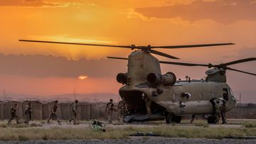 US Army soldiers board a CH-47 Chinook helicopter while departing a remote combat outpost known as RLZ near the Turkish border in northeastern Syria.