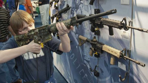 A boy looks at an assault rifle at an NRA convention. (AAP)