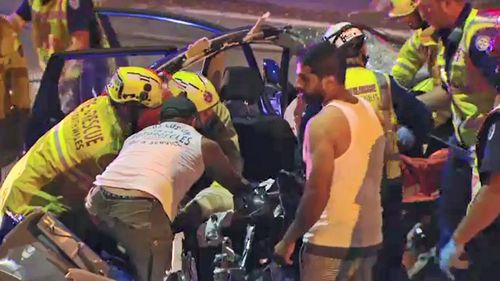Firefighters work to free trapped occupants of the sedan.