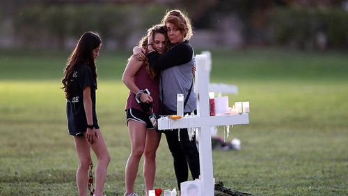 People hug as they pay homage at the memorial crosses, for the 17 deceased students and faculty at Marjory Stoneman Douglas High School. (AAP)