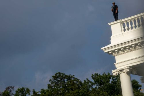 A US Secret Service police officer stands on the roof of the the White House