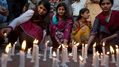 Members of a civil society group light candles during a vigil for the victims of Sunday's suicide bombing. (AP)