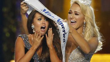 Cara Mund is given the Miss America sash by the previous winner.