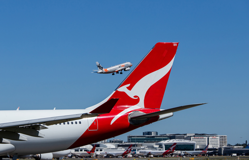 Qantas aircraft on tarmac and Jetstar plane flying in the background