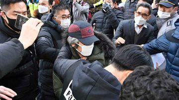 Cho Doo-soon, centre, escorted by police officers, arrives home in Ansan, South Korea.