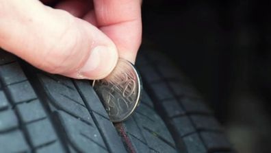 Man using 20 cent coin to check wear on tyre treads