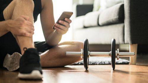 Man on phone workout at home weights