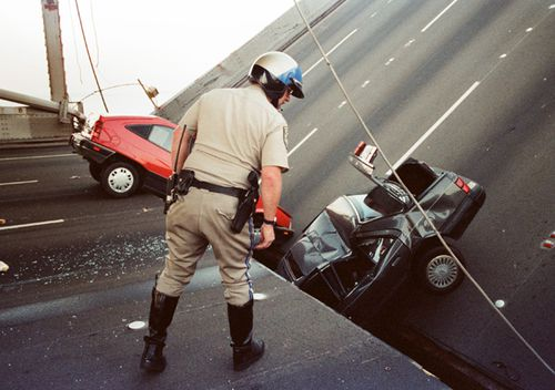 In this 1989 file photo, a California Highway Patrol officer checks the damage to cars that fell when the upper deck of the Bay Bridge collapsed onto the lower deck after the Loma Prieta earthquake in San Francisco.