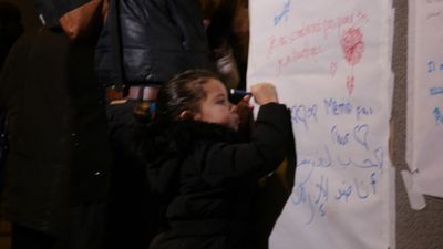 A young girl signs her name on a tribute outside Le Petit Cambodge. (Jack Hawke, 9News.com.au)