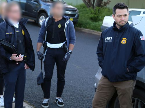 An official with US Homeland Security is pictured NSW Police and Australian Border Force officers as a search warrant was executed on the property.