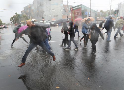 People are seen in Flinders Street, Melbourne, dashing from the rain. (AAP)