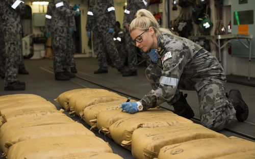 Leading Seaman Naval Police Coxswain Jamie Janes as she numbers narcotic parcels seized by HMAS Warramunga during operations in the Middle East in December last year. (AAP)