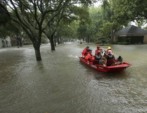 A Coast Guard rescue team evacuates people from a neighbourhood inundated by floodwaters. (AP)