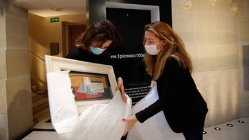 """Raffle organisers Peri Cochin, left, and Arabenne Reille unbox the painting """"Nature morte"""" by Picasso at Christie's auction house"""