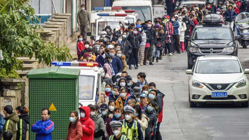 People line up to buy face masks from a medical supply company in Nanning in southern China's Guangxi Zhuang Autonomous Region.
