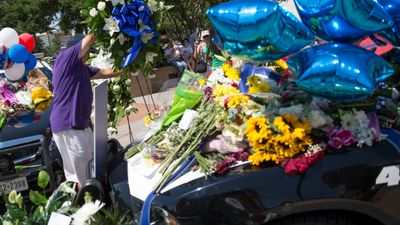 Flowers cover a police car at a memorial outside the Dallas police headquarters.