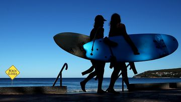 Surfers walk past a 'Beach Closed' sign at Manly Beach in Sydney.