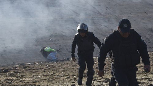 A Honduran migrant lies on the riverbank as Mexican police move away from tear gas fired by U.S. agents at the Mexico-U.S. border in Tijuana, Mexico.