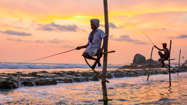 Traditional fishermen work as the sun sets near Galle.