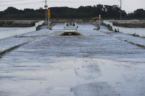 A truck drives through a flooded street Monday, Oct. 14, 2019, in Kawagoe City, Japan. Hagibis dropped record amounts of rain for a period in some spots, according to meteorological officials, causing more than 20 rivers to overflow. Some of the muddy waters in streets, fields and residential areas have subsided. But many places remained flooded, with homes and surrounding roads covered in mud and littered with broken wooden pieces and debris. (AP Photo/Eugene Hoshiko)