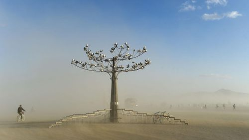 """A """"burner"""" rides next to a sculpture during a dust storm at Burning Man in the Black Rock Desert near Gerlach, Nevada. (AP)"""
