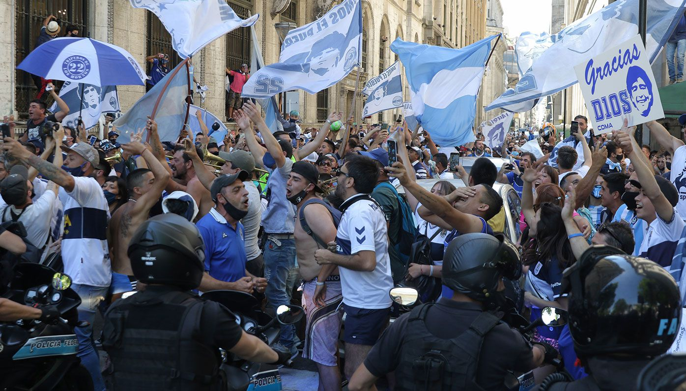 Fans sing and wave flags as the police tries to contain them during Diego Maradona's funeral in Buenos Aires, Argentina.