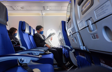 A passenger wearing a face mask seen reading a news paper inside the ANA plane