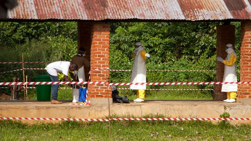 Health workers are sprayed with chlorine after leaving the isolation ward to diagnose and treat suspected Ebola patients. Picture: AP