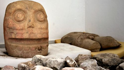 A skull-like stone carving and a stone trunk depicting the Flayed Lord, a pre-Hispanic fertility god depicted as a skinned human corpse.